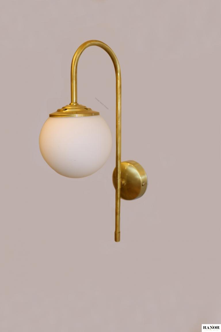 """מנורת קיר עשויה מחומר פליז עבודת יד, כדור זכוכית חלבי קוטר 12 ס""""מ, המנורה עוצבה על ידי המעצב יעקב ארז, ייצור כחול לבן מבית רנאור עיצובי תאורה."""