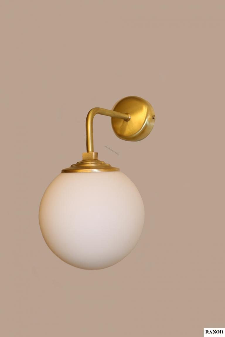 """מנורת קיר עשויה מחומר פליז עבודת יד, כדור זכוכית חלבי קוטר 15 ס""""מ, המנורה עוצבה על ידי המעצב יעקב ארז, ייצור כחול לבן מבית רנאור עיצובי תאורה."""